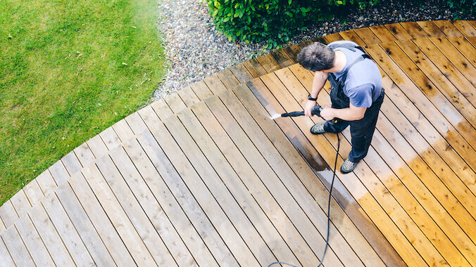 a man cleans the wood deck Deck Cleaning Royal Wash