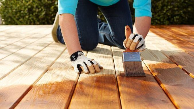 a man stains the wood deck Deck Staining Royal Wash