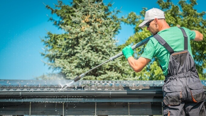 a man cleans roof and gutters Royal Wash